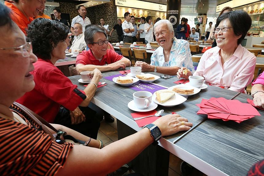 NTUC secretary general Lim Swee Say (fourth from left) speaks to members of the pioneer generation having bread and coffee at NTUC Foodfare food court in Ang Mo Kio hub on Oct 13, 2014. -- ST PHOTO: NEO XIAOBIN