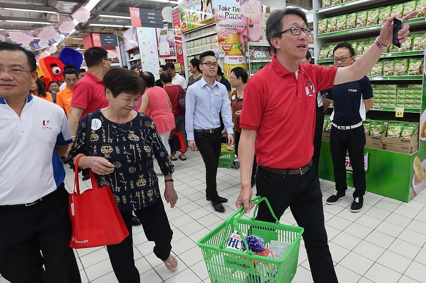 NTUC secretary general Lim Swee Say (right, in red) carries the groceries of Madam Ng Ah Ping (second from left, in black), 80, and brings her to the designated priority queue together with NTUC Fairprice Co-operative Limited CEO Seah Kian Peng (far