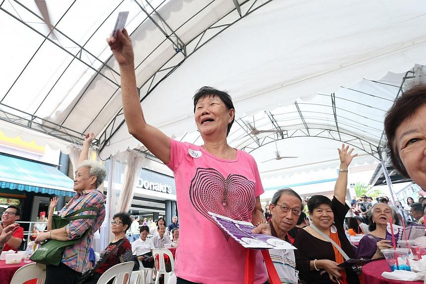 """Pioneers at a quiz segment at the launch of the 15-month """"Pioneers OK!"""" package, an initiative by the labour movement's social enterprise arm, at a ceremony at the Ang Mo Kio hub on Oct 13, 2014. -- ST PHOTO: NEO XIAOBIN"""