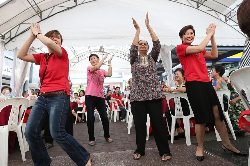 """Madam Ishentkaur (second from right), 67, gets up from her seat and dances impromptu to a flash mob performance during the launch of the 15-month """"Pioneers OK!"""" package, an initiative by the labour movement's social enterprise arm, at a ceremony at t"""