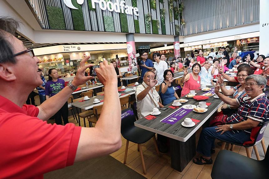 NTUC secretary general Lim Swee Say (left) takes a photograph of a group of pioneers having bread and coffee at NTUC Foodfare food court in Ang Mo Kio hub on Oct 13, 2014. -- ST PHOTO: NEO XIAOBIN