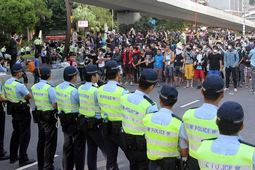 Police officers (front) and pro-democracy demonstrators face off near the government offices in Hong Kong on Oct 13, 2014. -- PHOTO: AFP