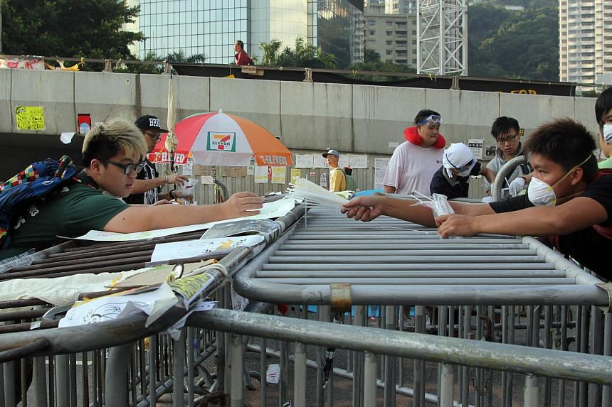 Pro-democracy demonstrators put up barricades near the government offices in Hong Kong on Oct 13, 2014. -- PHOTO: AFP