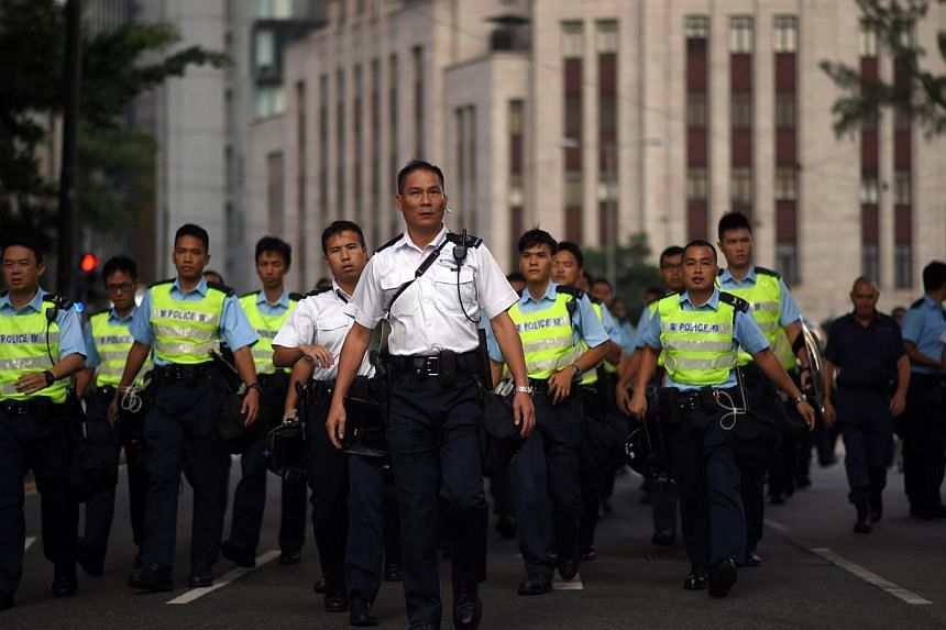 Police officers gather near a pro-democracy protest in the Central district of Hong Kong on Oct 13, 2014. -- PHOTO: AFP