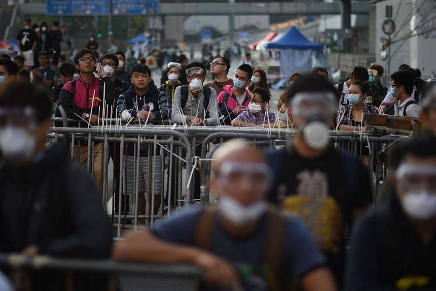 Pro-democracy protesters stand next to barricades as police officers gather in the Central district of Hong Kong on Oct 13, 2014. -- PHOTO: AFP