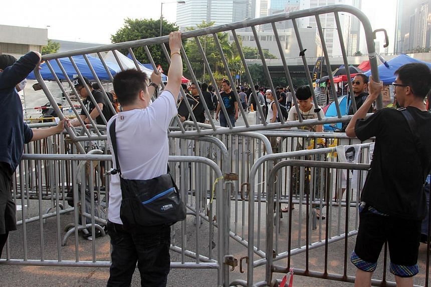 Pro-democracy demonstrators put up barricades near the government offices in Hong Kong on October 13, 2014. -- PHOTO: AFP