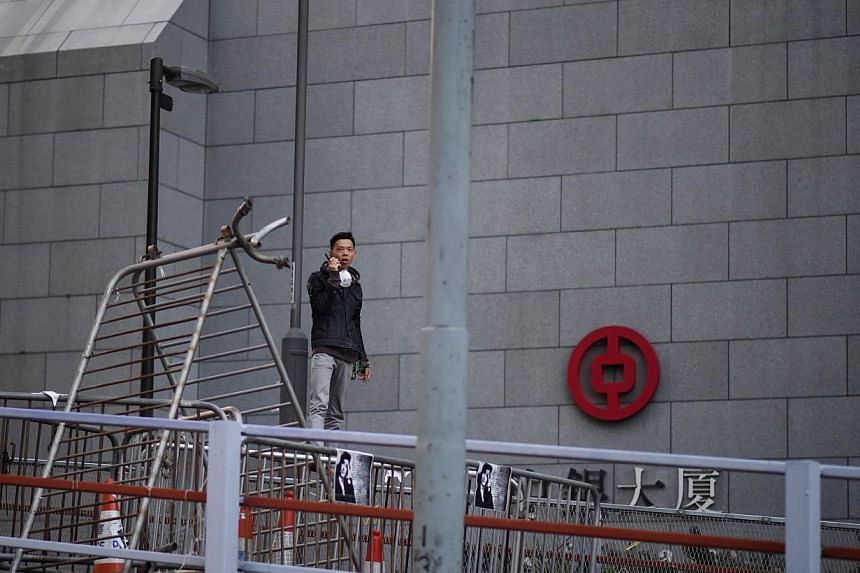 A pro-democracy protester stands on barricades as police officers gather in the Central district of Hong Kong on Oct 13, 2014. -- PHOTO: AFP
