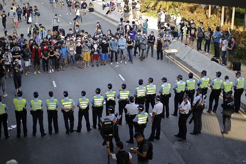 Police stand in a cordon facing pro-democracy protesters at the main protest site in Admiralty in Hong Kong on Oct 13, 2014. -- PHOTO: REUTERS