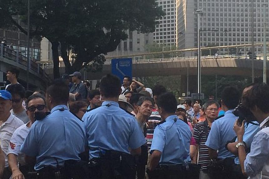 Police standing between protesters and their opponents. -- ST PHOTO: LI XUEYING