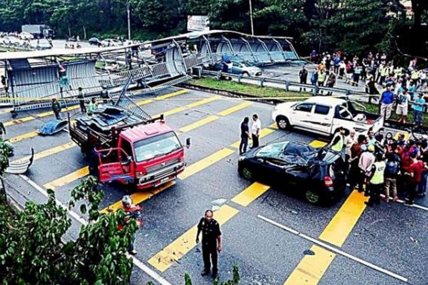 Motorists gathering to look at the collapsed roof and railings of a pedestrian bridge that flew off due to a thunderstorm along the Pasir Gudang Highway in Johor Baru, Malaysia, on Oct 12, 2014. -- PHOTO: THE STAR/ASIA NEWS NETWORK