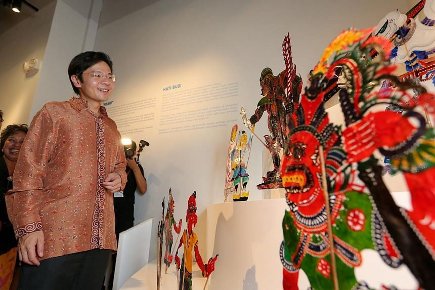 Minister Lawrence Wong looking at a display of fusion wanyang kulit that will be used in a shadow-play performance using the storyline and characters from Star Wars. A three-week long festival showcase at the Malay Heritage Centre for traditional and