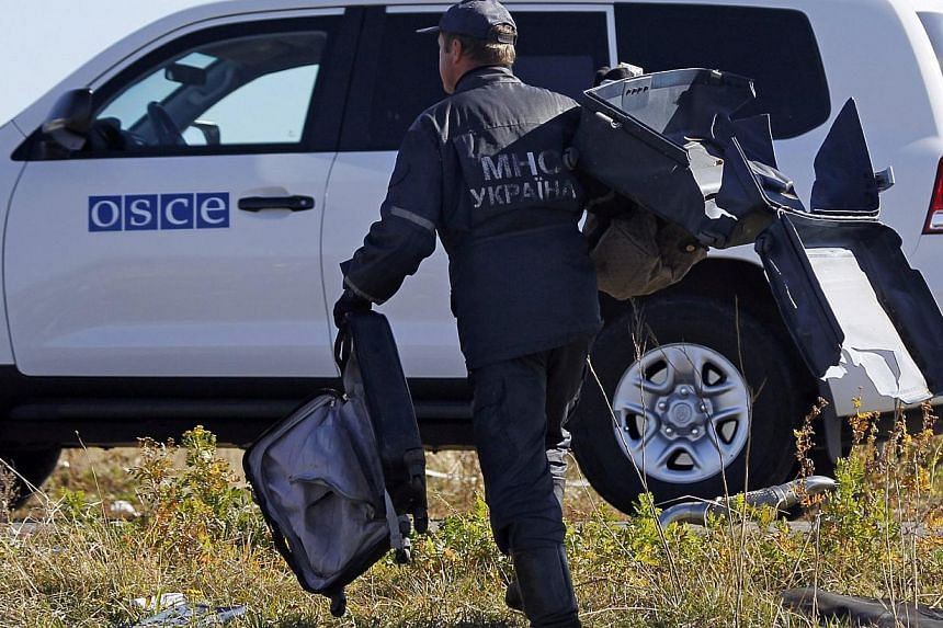 Four Dutch experts visited the crash site of Malaysia Airlines Flight MH17 in east Ukraine on Monday to help recover personal belongings of victims despite fighting between government troops and separatist rebels nearby. -- PHOTO: REUTERS