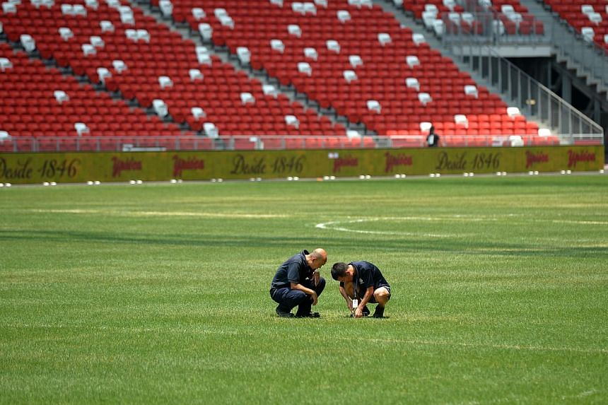 Groundsmen checking the pitch at the Sports Hub. -- ST PHOTO:JAMIE KOH