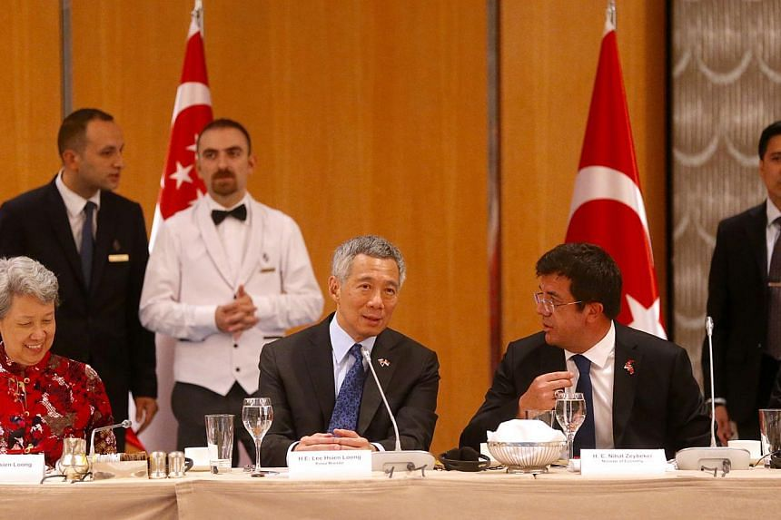 PM Lee Hsien Loong (centre) speaking to Turkey Minister for Economy Nihat Zeybekci (right) at the luncheon meeting with CEOs from Turkey's leading companies, as well as representatives of Singapore businesses. -- ST PHOTO: CHEW SENG KIM
