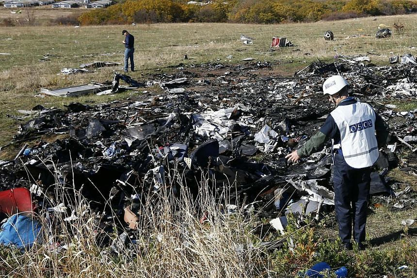 Members of the recovery team work at the site where the downed Malaysia Airlines flight MH17 crashed, near the village of Hrabove (Grabovo) in Donetsk region, eastern Ukraine on Oct 13, 2014. -- PHOTO: REUTERS