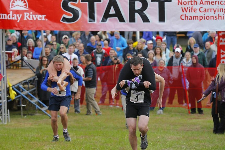 Contestants leave the starting line to compete in the North American Wife Carrying Championship at Sunday River ski resort in Newry, Maine on Oct 11, 2014. -- PHOTO: REUTERS