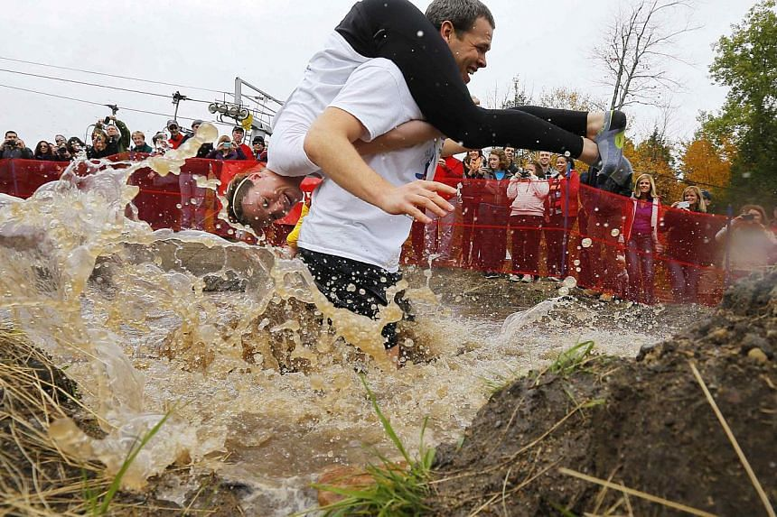 Seth Swanberg carries Lisa Swanberg through the water pit while competing in the North American Wife Carrying Championship at Sunday River ski resort in Newry, Maine on Oct 11, 2014. -- PHOTO: REUTERS
