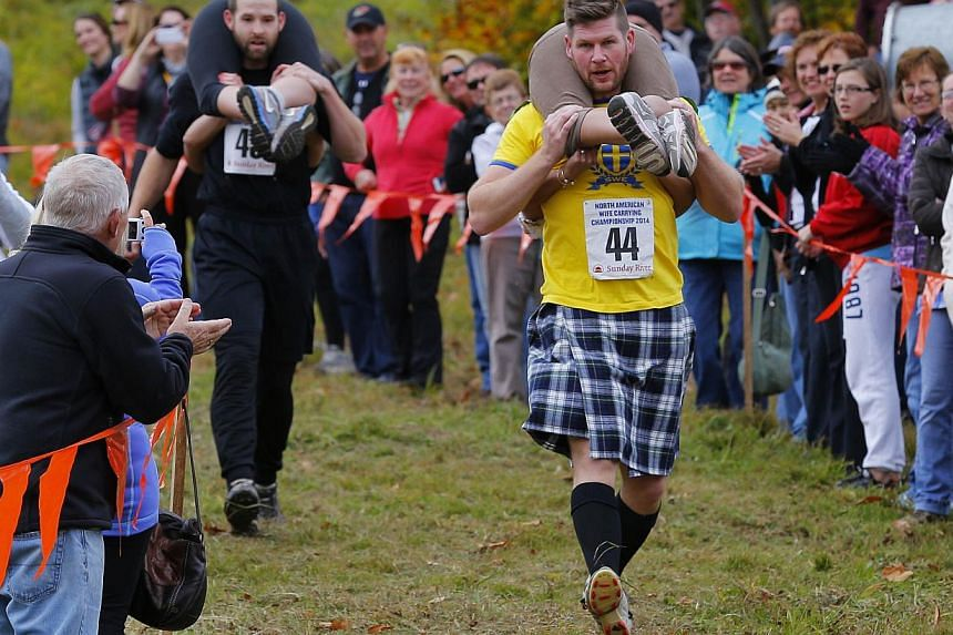 Christian Carlsson (front in yellow) carries Tuyet Nguyen ahead of Kevin Chamberlain (rear), carrying Chantal Colpitts, in the North American Wife Carrying Championship at Sunday River ski resort in Newry, Maine on Oct 11, 2014. -- PHOTO: REUTERS