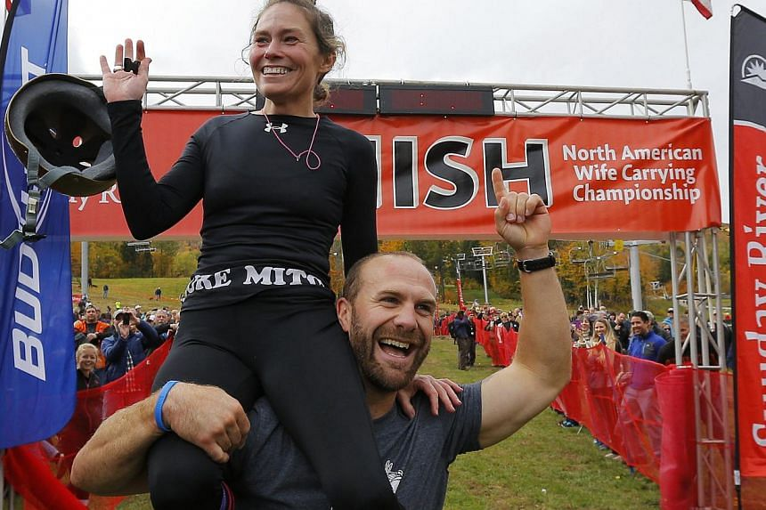 Christina Arsenault and Jesse Wall (right) celebrate after winning the North American Wife Carrying Championship at Sunday River ski resort in Newry, Maine on Oct 11, 2014. -- PHOTO: REUTERS