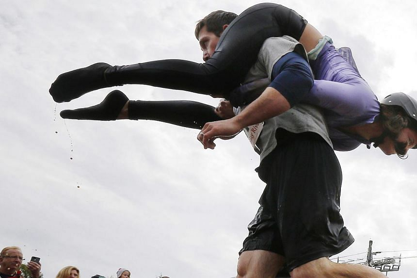Nathan Johnson carries Tia Johnson out of the water pit while competing in the North American Wife Carrying Championship at Sunday River ski resort in Newry, Maine on Oct 11, 2014. -- PHOTO: REUTERS