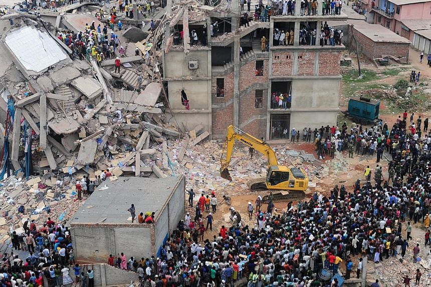 In this photograph taken on April 25, 2013, Bangladeshi volunteers and rescue workers are pictured at the scene after an eight-storey building collapsed in Savar on the outskirts of Dhaka. -- PHOTO: AFP