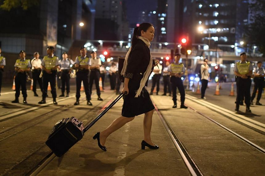 A pedestrian crosses a street alongside security personnel during ongoing pro-democracy protests Hong Kong on Oct 13, 2014. -- PHOTO: AFP