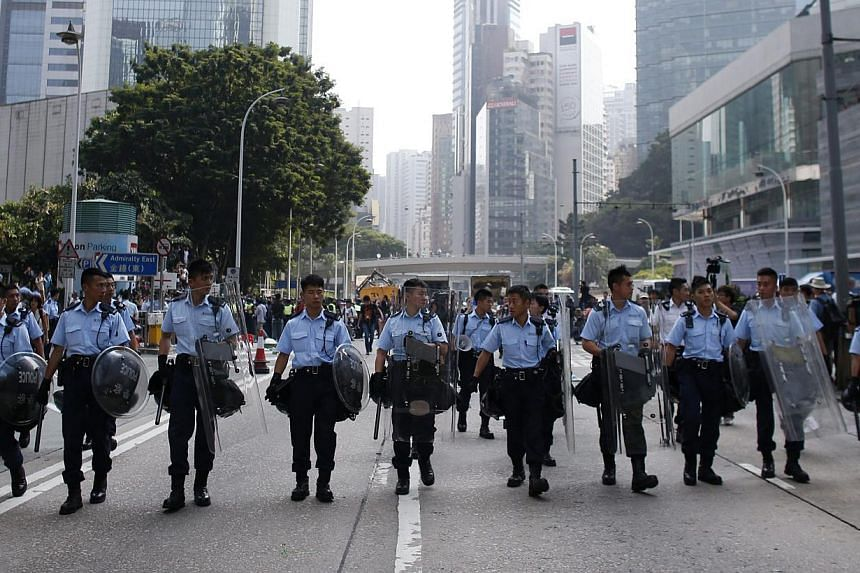 Police officers take control of Queensway Road as they remove barricades from a protest site in Admiralty near the government headquarters in Hong Kong on Oct 14, 2014. -- PHOTO: REUTERS