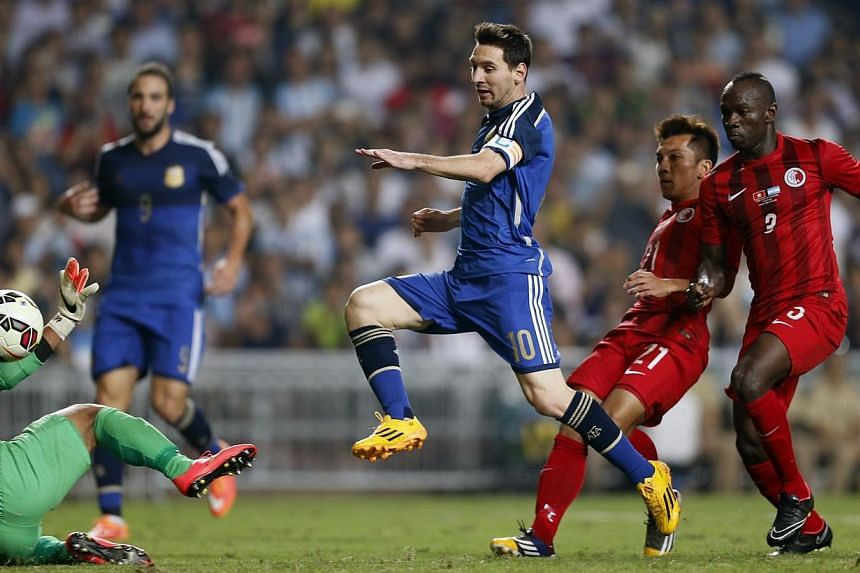 Argentina's Lionel Messi (centre) scores his first goal during their international friendly soccer match against Hong Kong, in Hong Kong on Oct 14, 2014. Argentina strolled to a 7-0 friendly win over Hong Kong on Tuesday, with superstar Messi and Nap