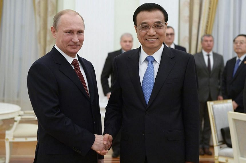 Russia's President Vladimir Putin (left) shakes hands with China's Prime Minister Li Keqiang during their meeting at the Kremlin in Moscow on Oct 14, 2014. -- PHOTO: AFP