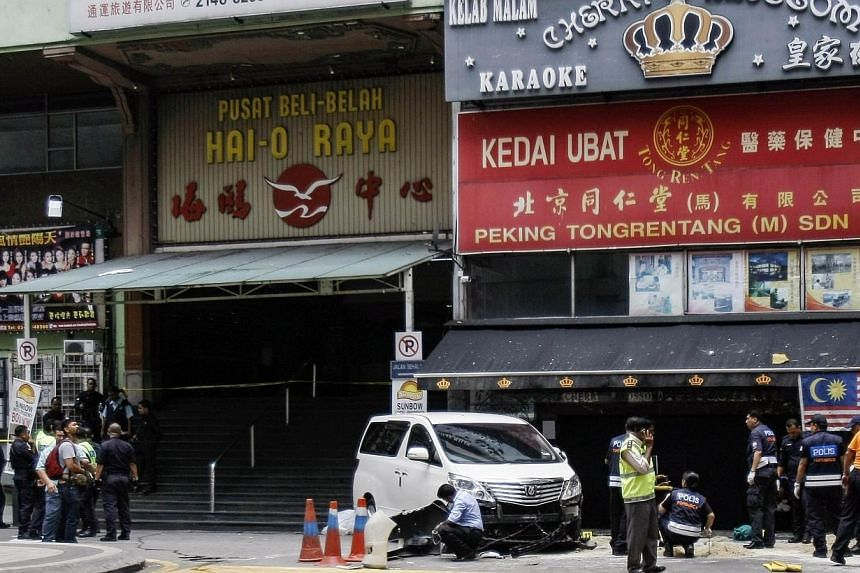 Police work at the scene of a grenade attack outside a shopping centre at Bukit Bintang in Kuala Lumpur on Oct 9, 2014.A gambling kingpin believed to be the target of assassination outside a karaoke lounge in Malaysia which killed a man gave hi