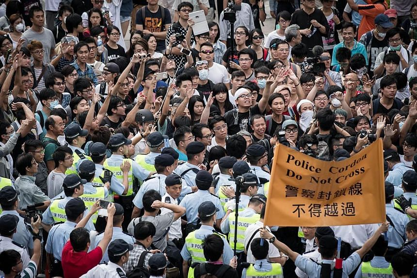 Policemen cordon an area where pro-democracy demonstrators confronted anti-occupy protesters (not in picture) in the Admiralty district of Hong Kong on Oct 13, 2014.Attacks by masked men on Hong Kong's pro-democracy protesters have shone an unc
