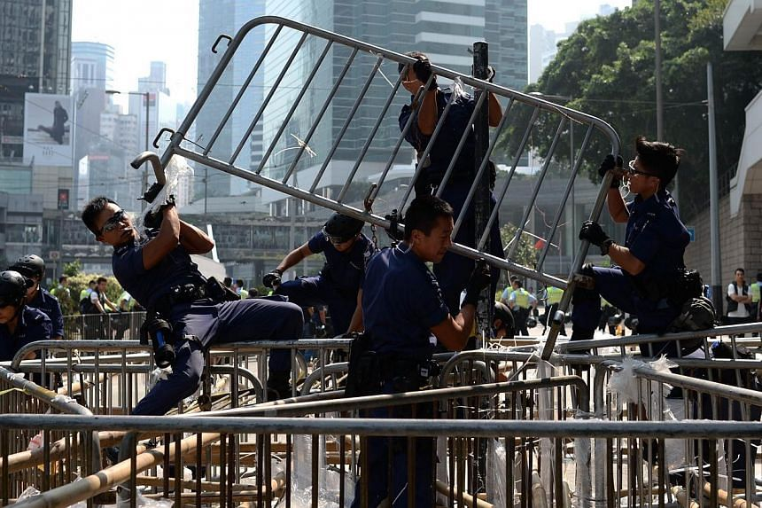 Police officers remove barricades of pro-democracy protestors in the Admiralty district of Hong Kong on Oct 14, 2014. -- PHOTO: AFP