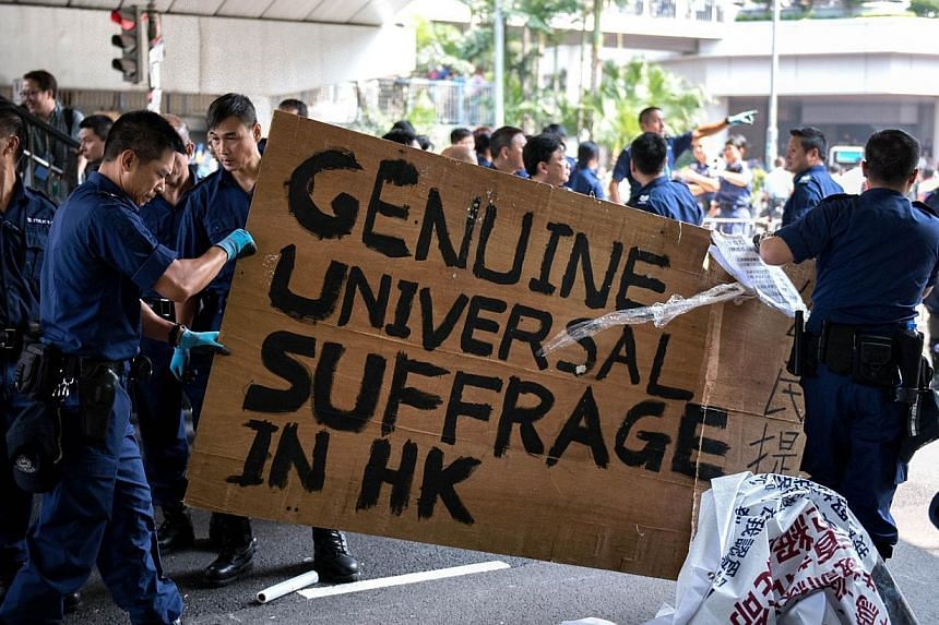 Police officers carry a sign that calls for Genuine Universal Suffrage in HK as they dismantle a pro-democracy protest barricade in Hong Kong on Oct 14, 2014. -- PHOTO: AFP