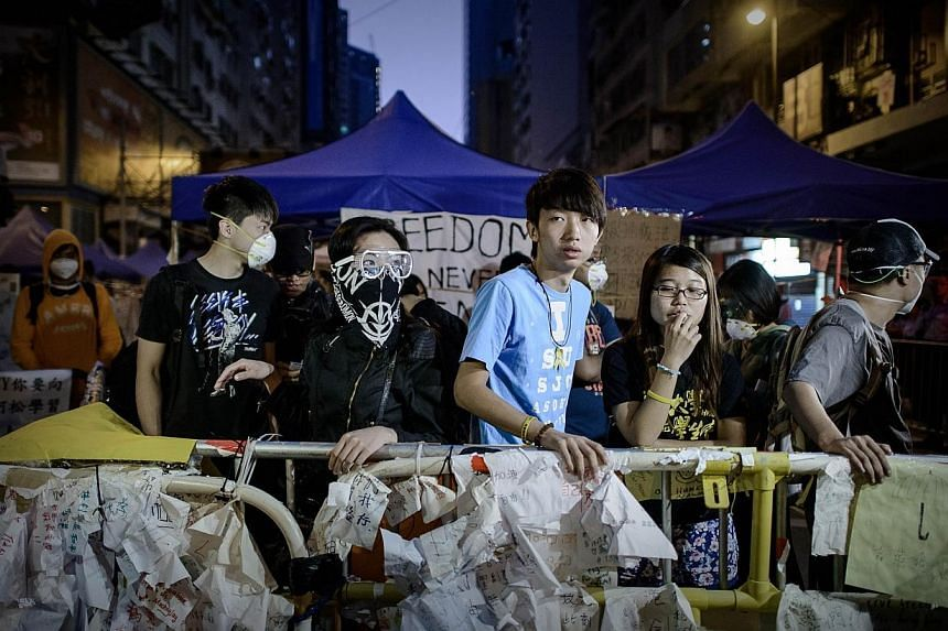 Pro-democracy protesters look on as police forces take positions during the removal of barricades in Hong Kong at dawn on Oct 14, 2014. -- PHOTO: AFP