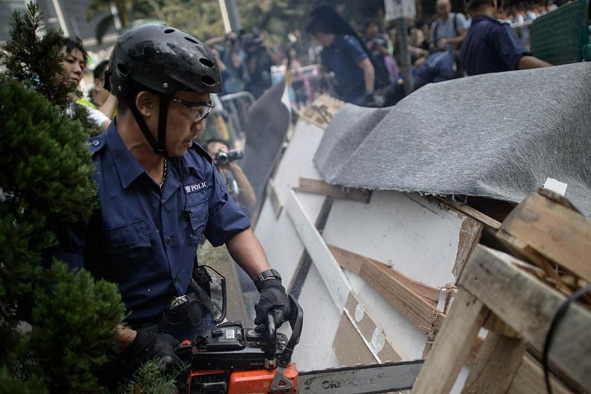 Police use a chainsaw to remove barricades erected by pro-democracy protesters in the Admiralty district of Hong Kong on Oct 14, 2014. -- PHOTO: AFP