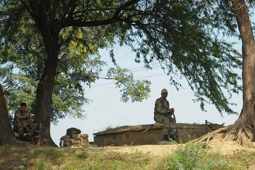 Indian Border Security Force soldiers keep watch following cross-border firing between Pakistan and Indian troops at Ramgarh, about 35 kms from Jammu, on Oct 11, 2014.Senior Pakistani and Indian military officials spoke Tuesday by hotline after
