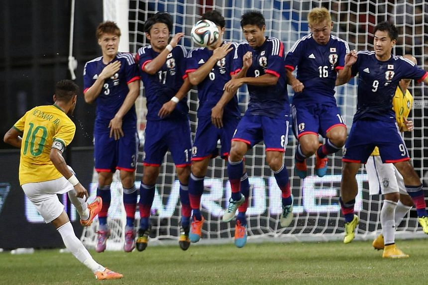 Brazil's Neymar (left) takes a free-kick against Japan during their friendly soccer match at the national stadium in Singapore on Oct 14, 2014. -- PHOTO: REUTERS