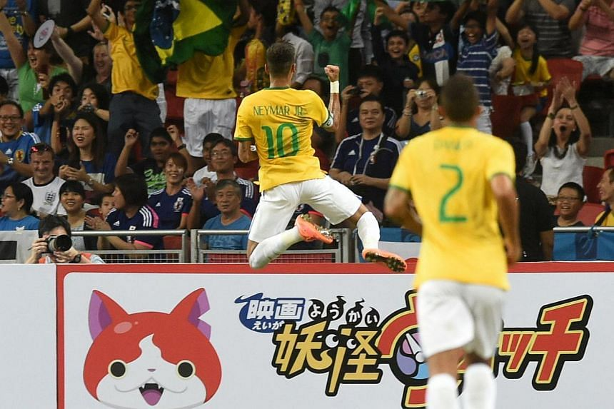 Brazil's forward Neymar celebrates his first goal in a friendly football match against Japan team at the National stadium in Singapore on Oct 14, 2014. -- PHOTO: AFP