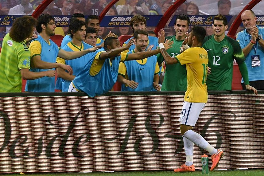 Brazil's forward Neymar (front) celebrates his first goal with team mates in a friendly football match against Japan team at the National stadium in Singapore on Oct 14, 2014. -- PHOTO: AFP