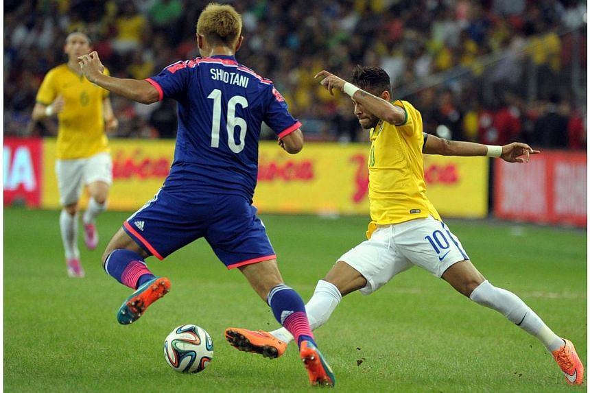 Japan's Shiotani Tsukasa (left) and Brazil's forward Neymar compete for the ball during their friendly football match at the National Stadium in Singapore on Oct 14, 2014. -- PHOTO: AFP