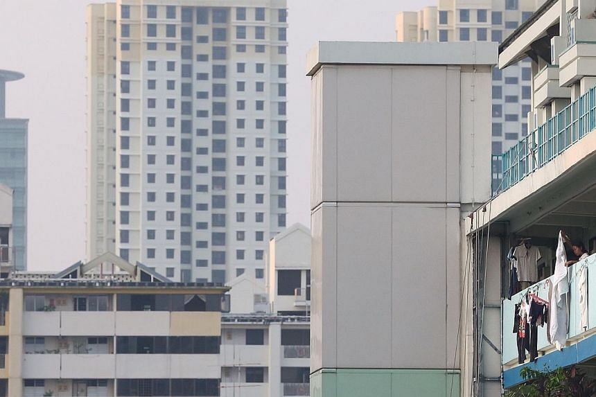 A woman dries her laundry along the HDB flat corridor in Toa Payoh at 7.20am on Oct 14, 2014.  -- ST PHOTO: NEO XIAOBIN