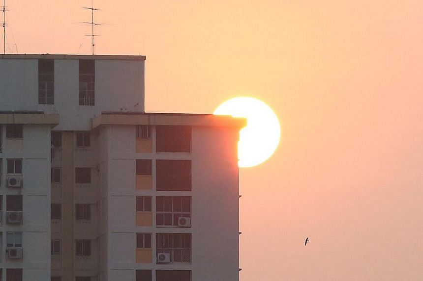 A slight haze causes a red sky as the sun rises against a HDB block at 7.05am on Oct 14, 2014.  -- ST PHOTO: NEO XIAOBIN