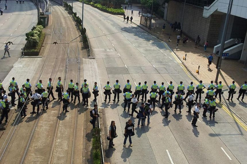 Police officers forming a line along Queensway, near the main protest site at Hardcourt Road. -- ST PHOTO: PEARL LIU