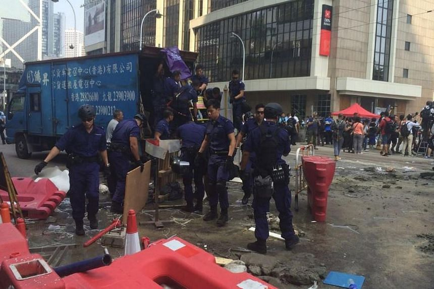 Police armed with bolt cutters, chainsaws and sledgehammers made a renewed attempt on Tuesday to remove barricades along a stretch of the main protest site held by pro-democracy demonstrators for the past fortnight. -- ST PHOTO: LI XUEYING