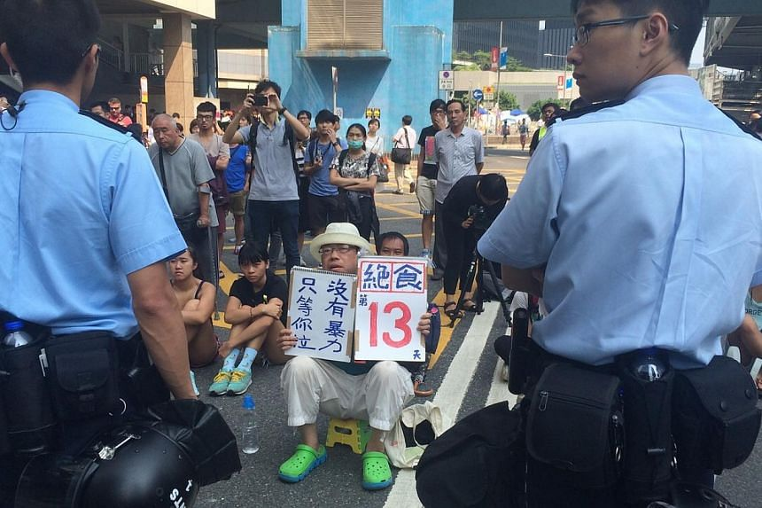 A protester holding a sign declaring his hunger strike as part of the demonstration.-- ST PHOTO: LI XUEYING