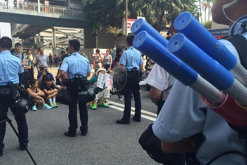 Police with helmets and shields forming a line to prevent protesters and public from stopping the operation.-- ST PHOTO: LI XUEYING