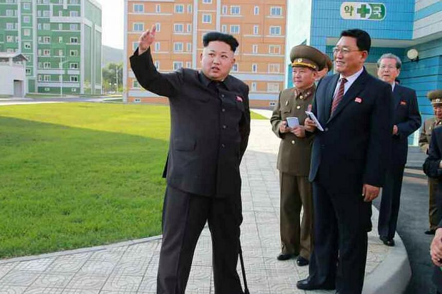 This picture taken from North Korean paper Rodong Sinmun on Oct 14, 2014 shows North Korean leader Kim Jong Un (left) during an inspection tour of a newly-built housing complex in Pyongyang. -- PHOTO: AFP