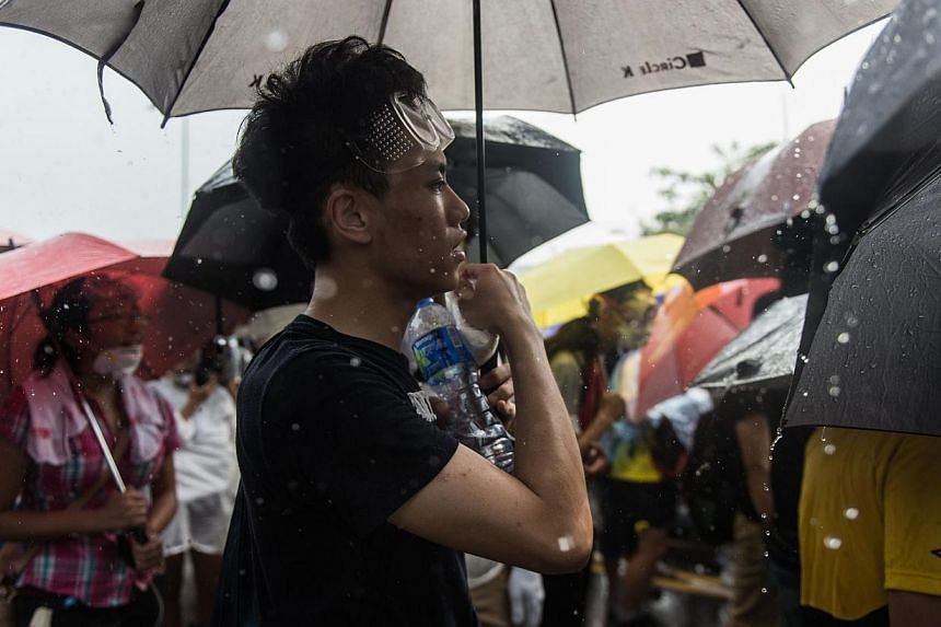 Hong Kong protesters singing Under A Vast Sky in the rain. -- PHOTO: AGENCE FRANCE-PRESSE