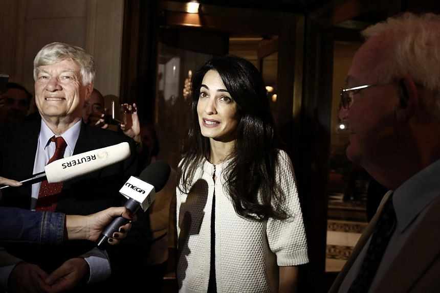 Human rights lawyer Amal Alamuddin Clooney (middle) with Geoffrey Robertson (left), head of Doughty Street Chambers, and David Hill, head of the International Committee for the Reunification of the Parthenon Marbles, on arrival at a hotel in Athens,
