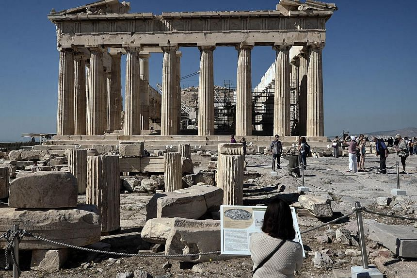 Tourists visit the Parthenon Temple at the Acropolis hill in Athens, Greece on Oct 12, 2014. -- PHOTO: AFP